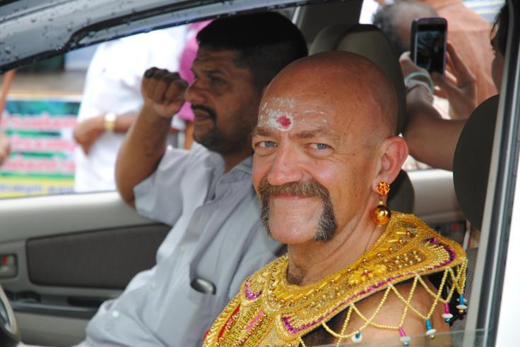 La storia è complicata, come lo sono le storie di dei, per cui la faccio breve. Durante il regno del Re Mahabali il Kerala, regione all'estremo sud del subcontinente indiano, prosperava come mai prima. Il Re era così amato e benvoluto dal suo popolo che gli dei guardavano con invidia e irritazione la sua fortuna. Per questo motivo Visnù tese un tranello a Mahabali costringendolo a una sfida di canto e poesia che il re, ovviamente, perse. Come pena per la sconfitta il re fu scaraventato negli inferi ma ottenne di potere visitare una volta all'anno il suo amato popolo. La festa di Onam, che si celebra circa a metà settembre è la festa nazionale del Kerala ed è considerata la festa dell'abbondanza e del raccolto. In tutte le città di questa Provincia Indiana si svolgono innumerevoli celebrazioni, una delle quali consiste nella sfilata del <re Mahabali per le strade della città. Durante la sfilata, il Re risalito per un giorno dagli inferi, saluta i suoi amati sudditi e la persona che incrocia lo sguardo con quello del re avrà fortuna e prosperità. Ero in Kerala proprio durante le celebrazioni di Onam, per una campagna vaccinale antirabbica e, con gli altri volontari, abbiamo deciso di partecipare alla sfilata formando un nostro gruppo di figuranti. Così noleggiamo i vestiti e ci uniamo alla sfilata della città di Palai, dove il giorno dopo saremmo andati a catturare e vaccinare cani randagi. Otre 30° con una umidità feroce, due chilometri di sfilata circondati da ali di folla festante e incredula nel vedere degli occidentali vestiti con i loro vestiti celebrare una festa così cara a questa gente. La sfilata si conclude in un teatro caldissimo e gremito, una moltitudine urlante, festosa e stupefatta nel vedere un Re Mahabali con gli occhi azzurri. A sorpresa, arriva l'ospite d'onore, il Ministro delle Finanze del Kerala che si produrrà in un interminabile discorso prima di premiare i tre migliori figuranti de Re. Quando mi hanno chiamato sul palco non sapevo se ridere o