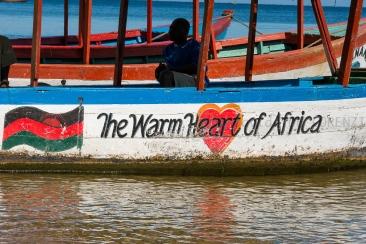 """Il Lago Nyasa, anche conosciuto con il nome di Lago Malawi, è il terzo lago più grande d'Africa e il nono più grande del mondo. Fu scoperto da Livingstone che lo battezzò con il meraviglioso nome di """"Nyasa"""", ovvero """"lago di stelle"""" per la stupefacente brillantezza della sua superficie. Da quel lontano 1859 ad oggi ben poco è cambiato attorno alle rive di questo lago subequatoriale che rappresenta il confine orientale fra Malawi e Mozambico; le imbarcazioni a motore sono pochissime e gli insediamenti umani sono rappresentati per lo più da piccoli villaggi di pescatori che utilizzano canoe scavate nei tronchi e pagaie di foggia antica. Il pesce viene ancora pescato con reti gettate a mano durante la notte e ritirate alle prime luci dell'alba e tutta la vita di queste comunità si svolge sulle sponde del lago che funge, di volta in volta, da serbatoio di acqua utilizzata per cucinare o bere, zona dove lavarsi, lavare i panni e le poche suppellettili, gabinetto, area giochi per bambini, cantiere per la riparazione delle imbarcazioni, area per l'essiccazione del pesce e altro ancora… L'alba e il tramonto visti dalle sue rive regalano al viaggiatore colori, silenzi e atmosfere alle quali non è più abituato, toccando corde profonde ed evocando memorie ancestrali di un remotissimo passato nel quale queste rive sono sono state la culla dell'umanità. Una ultima nota: nonostante le atmosfere da Paradiso Terrestre, è corretto ricordare come le acque del lago siano infestate da un parassita, la Bilhazia o Schistosoma, in grado di penetrare attraverso la cute integra di chi si bagna nelle acque vicine alla riva causando seri problemi di salute nelle popolazioni locali ma soprattutto nell'incauto viaggiatore che decida di fare un tuffo nelle acque cristalline del lago. In aggiunta, la zona è endemica per Malaria e Rabbia. Non sono tutte stelle quelle che luccicano…"""