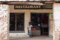I pochi ristoranti locali sono costituiti da piccole costruzioni in muratura, privi di infissi e di luce elettrica. Qualche tavolo e sedia autocostruiti, fuochi di carbone sul retro sui quali bollono pentoloni con patate e pesce, tinozze con acqua per risciacquare frettolosamente piatti e posate. Una parte del ristorante è adibita a magazzino dove si vende di tutto, dai chiodi ai rimedi locali per la malaria o le infezioni cutanee.