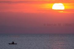 Un pescatore si attarda al tramonto con la sua canoa sulle acque oramai scure del lago, mentre il cielo e le nuvole sono in fiamme.