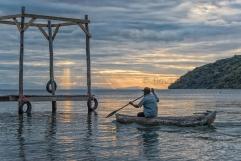 Un pescatore ritorna al suo approdo alle prime luci dell'alba.
